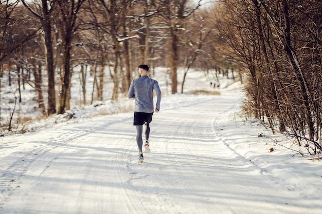 겨울에 눈 덮인 길에서 자연 속에서 달리는 주자의 뒷모습. 건강한 라이프 스타일, 눈 덮인 날씨, 겨울 피트니스