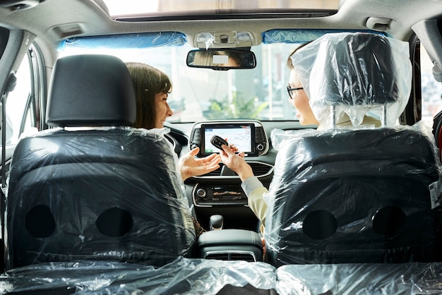 車に座って、新しい車から若い女性に鍵を与えるセールスマンの背面図