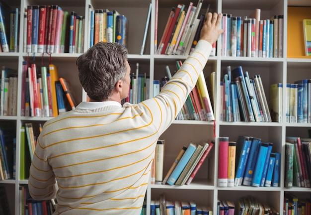 図書館で本を選択する学校教師の背面図