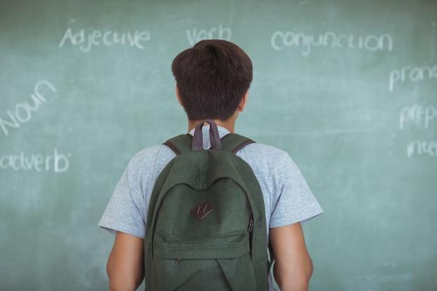 Вид сзади школьника с классной доской для чтения рюкзака в классе