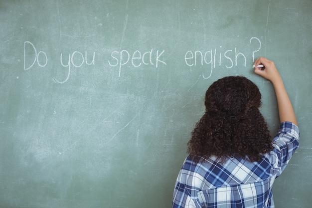 Вид сзади школьницы, притворяющейся учителем в классе