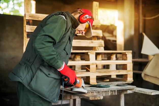 プロの制服を着た電動グラインダーツールで木材を燃やす上級大工の背面図。