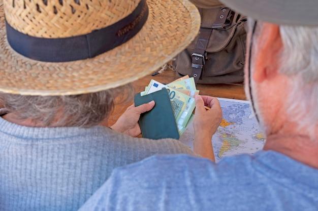 Вид сзади пожилой пары, планирующей путешествие по миру - активные пожилые каникулы, концепция бесплатного выхода на пенсию. деревянный стол с картой, деньгами, рюкзаком и паспортами