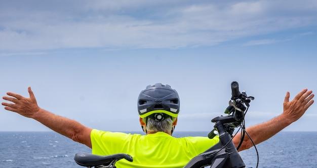 Вид сзади человека старшего велосипедиста, отдыхающего в море на скале после экскурсии с его электровелосипедом. руки вытянуты