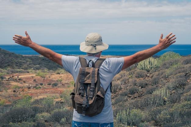 オープンアームで海の上の地平線を見ながら、アウトドアトレッキングを楽しんでいる年配の男性旅行者の背面図