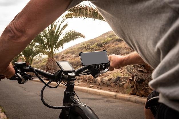 자전거와 함께 거리에서 실행하는 고위 사람들의 후면 볼 수 있습니다. 은퇴자를위한 e 자전거 솔루션. 길을 따라 장치와 휴대 전화. 산맥