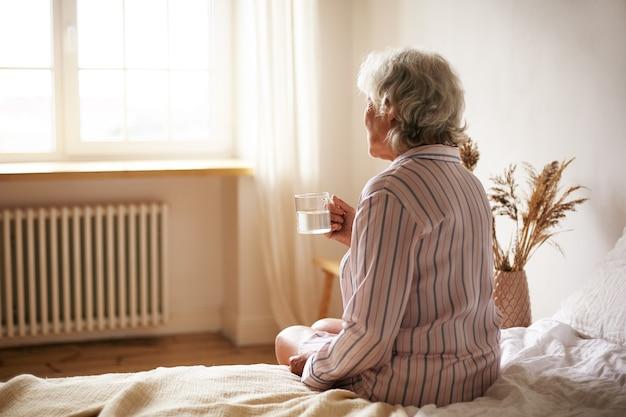 불면증으로 고통받는 수면제를 씻는 찻잔을 들고 회색 머리를 가진 수석 60 세 여성의 후면보기. 침실에 앉아 물으로 약을 복용하는 노인 은퇴 여성