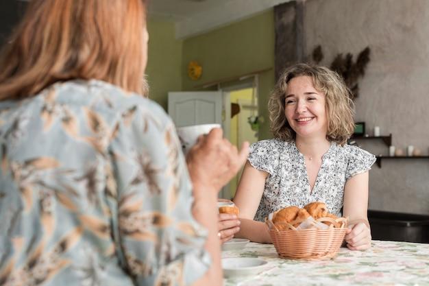 彼女の笑顔の壮大な娘とコーヒーを飲んでいる年配の女性の後姿