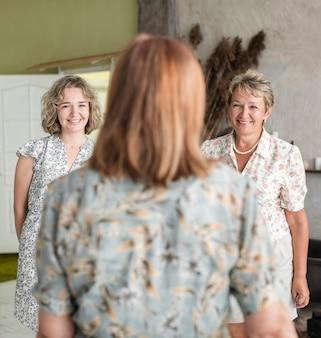 彼女の笑顔の娘と壮大な娘を見て年配の女性の後姿
