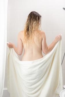 入浴後にタオルで拭くセクシーな女性の背面図