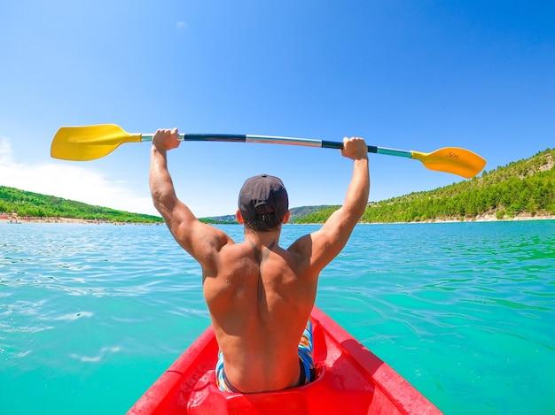 Вид сзади молодого человека без рубашки с татуировкой на спине, держащего весло с поднятыми руками в байдарке, исследующей спокойный тропический залив. человек путешествует на байдарке по озеру, любуясь природой