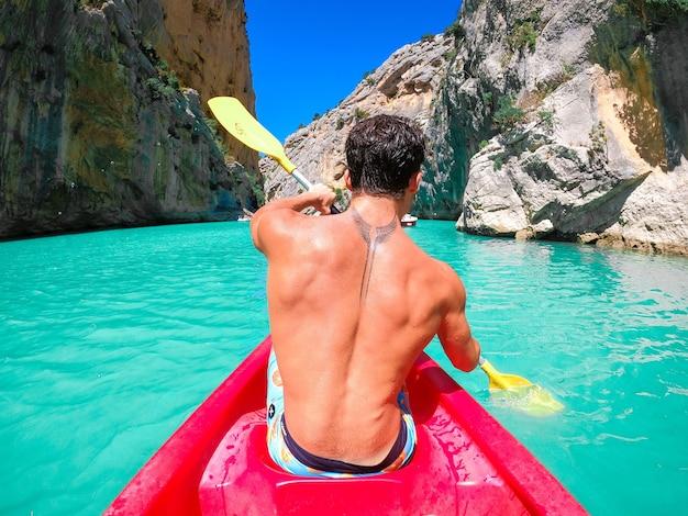 Вид сзади молодого человека без рубашки с татуировкой на спине, гребущего веслом в красном каяке, исследующего спокойный тропический залив на фоне горной долины. человек путешествует на байдарке по озеру, ведущему к горе