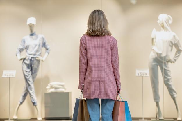 モールのショーウィンドウを見ている買い物袋と買い物中毒の背面図