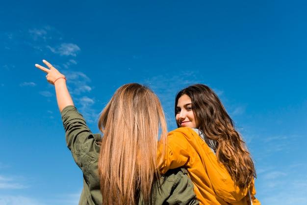 Вид сзади улыбается молодая девушка со своей подругой, gesturing знак победы