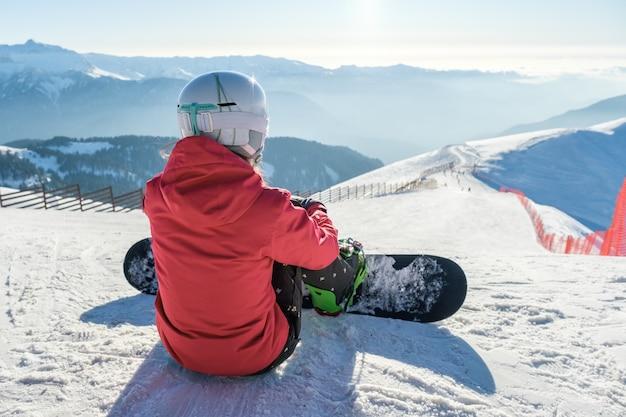 스키 슬로프 위에 장비가있는 스포츠웨어 스노 보더의 후면보기