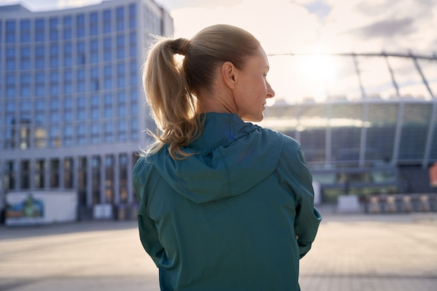 朝のトレーニングの準備ができて屋外に立っているスポーツウェアのスポーツ中年女性の背面図