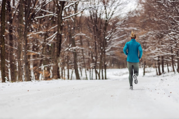 雪の降る天気で自然の中でジョギングするスポーツ選手の背面図。寒さ、雪、健康的な生活、フィットネス、健康的な習慣