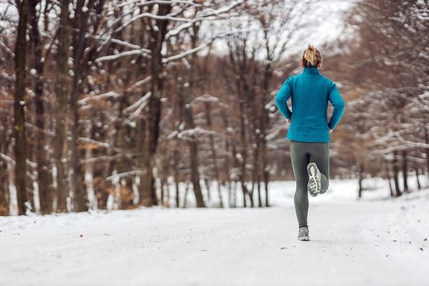 눈 덮인 날씨에 자연 속에서 조깅하는 sportswoman의 후면 볼 수 있습니다.