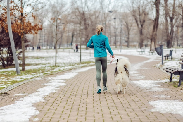 Вид сзади спортсменки, бегущей вместе со своей собакой в парке в снежную погоду. зимний фитнес, домашние животные, дружба, собаки