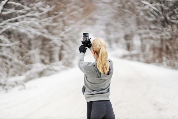 Вид сзади спортсменки, стоящей на природе в снежный зимний день и делающей селфи. технологии, тренды, зимний фитнес