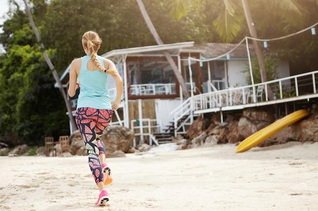 屋外ジョギング運動中に長い三つ編みでスポーティな女の子の背面図。深刻なマラソンの準備をして、朝のビーチを走るカラフルなレギンスで金髪の女性ジョガー。