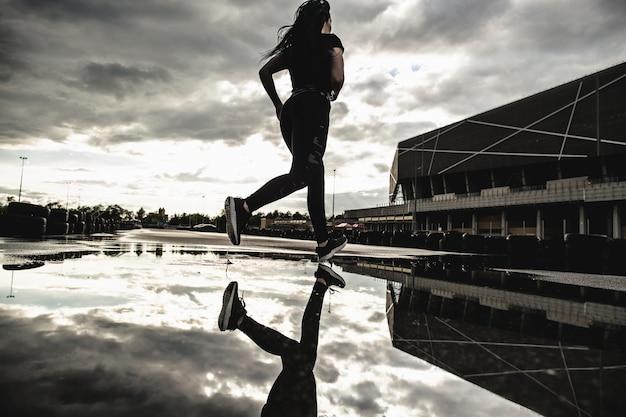 動いている強い運動の女性ランナーの背面図。雨上がりの屋外での朝のトレーニング。マラソンの準備をしている女性。