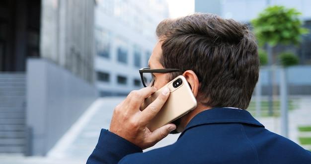 携帯電話で話し、街の通りを歩いているスタイリッシュなビジネスマンの背面図。街でスマートフォンで話すハンサムな男。背面図。