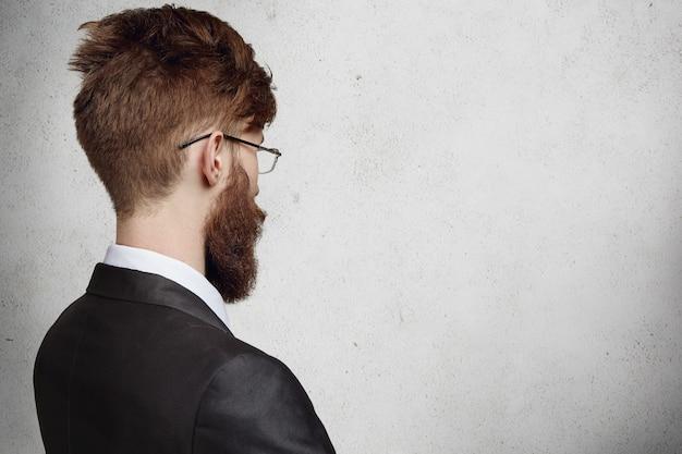 Вид сзади стильного молодого бизнесмена в очках, стоящего в офисе и смотрящего на пустую стену с копией пространства для вашей информации, мышления, идеи. выбор или решение.