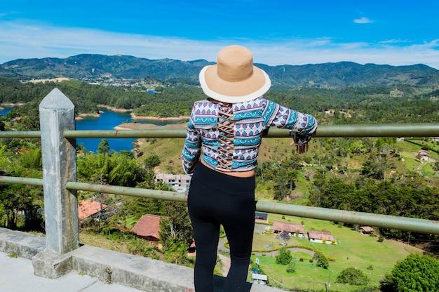 Вид сзади туристической женщины в шляпе, созерцающей природу в гуатапе, колумбия, с камня пенол