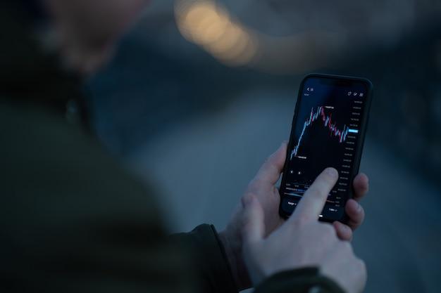 Вид сзади трейдера, отслеживающего данные фондового рынка в мобильном приложении для онлайн-торговли и инвестирования на смартфоне, стоя на открытом воздухе, выборочный фокус на руке, касаясь экрана с графиком форекс