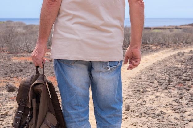 야외 여행을 즐기는 배낭을 들고 여행자 남자의 후면보기 바다 위의 수평선
