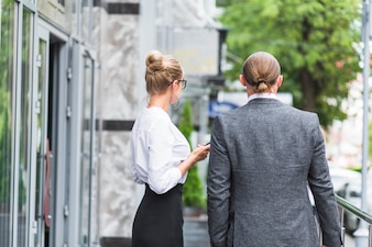 Rear view of two businesspeople standing outside office