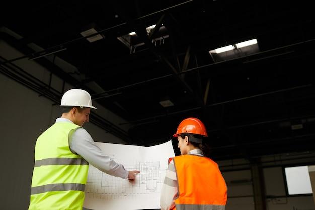 Вид сзади двух инженеров в светоотражающих жилетах, смотрящих на план и обсуждающих новый строительный проект в команде