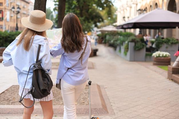 2人の女の子の背面図は地図で街を探索しています。