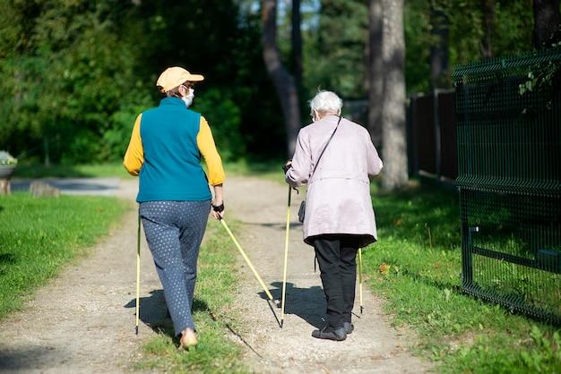 Covid-19 유행성 기간 동안 노르딕 워킹 폴과 함께 걷는 의료 마스크를 쓰고 두 노인 여성의 후면보기