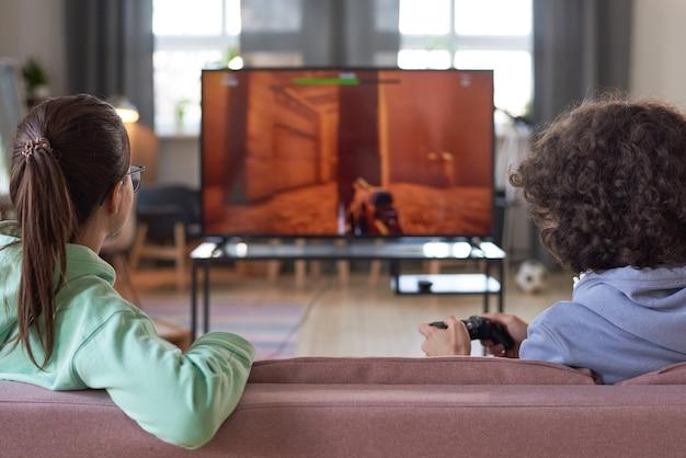 큰 tv 화면 앞 소파에 앉아 집에서 비디오 게임을 하는 두 십대의 뒷모습