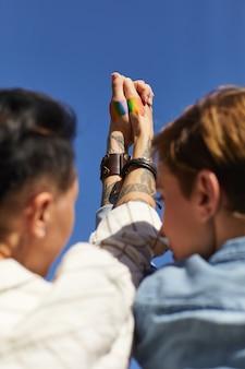 彼らがレズビアンの愛を促進する手をつないでいる2人の女性の背面図