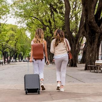 Вид сзади двух молодых женщин-туристов, гуляющих с ее багажом на улице