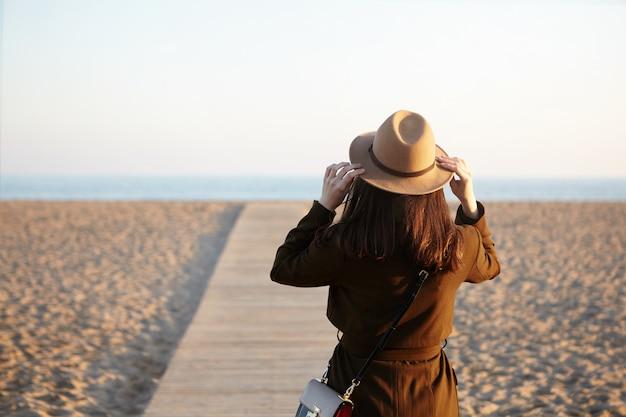 인식 할 수없는 갈색 머리 여자의 후면보기 모자, 코트와 어깨 가방을 입고 해변을 따라 산책로에 서서 좋은 따뜻한 하루를 즐기고, 열심히 일한 후 그녀의 마음을 만들기 위해 바다에 왔습니다.