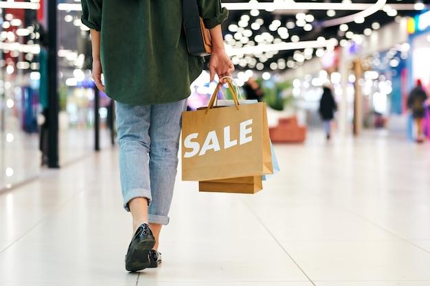 ショッピングモールの上を歩きながら買い物袋を運ぶジーンズの認識できない女性の背面図