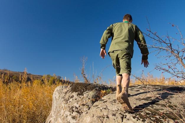 青い空を背景にキャンプエリアで古い大きな岩の上を歩いている白いボーイスカウトの背面図。