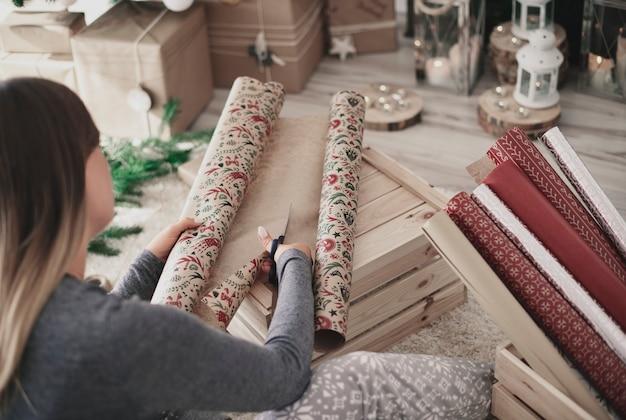 クリスマスの紙を切る女性の背面図