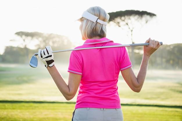 彼女のクラブを保持している女性ゴルファーの背面図