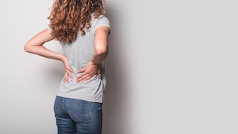 Rear view of woman having backache against gray background
