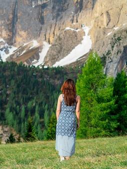 Вид сзади женщины в платье стоит на зеленой лужайке с видом на горы, доломиты, италия