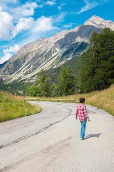 山道を歩いてニット帽とチェックのシャツを着た女性の背面図。雪に覆われた山の近くの道路上の女性を背景に。山道から自然を眺める女性ハイカー
