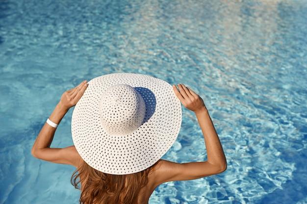 화창한 날에 수영장 근처에 앉아 흰 모자에있는 여자의 뒷 모습. 바다 여행 컨셉