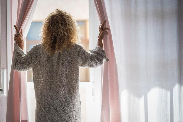 Вид сзади женщины открытия шторы и глядя через окно. женщина открывает занавески по утрам. спина женщин открывает шторы и любуется видом на улицу из окна дома