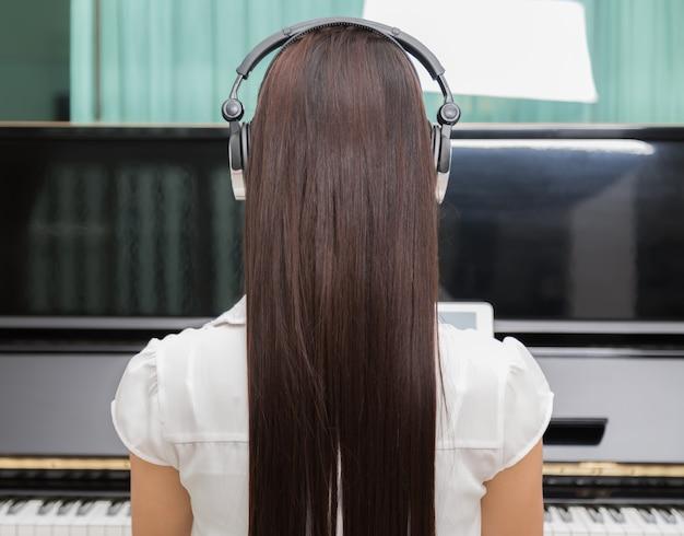 Вид сзади женщина играет фортепиано