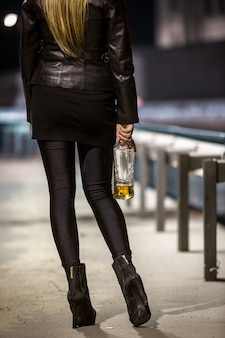 위스키 병 거리에 포즈를 취하는 여자의 뒷 모습